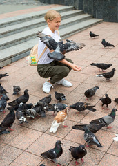 Teenager girl feeds the pigeons