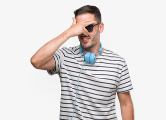 Handsome young man wearing headphones peeking in shock covering face and eyes with hand, looking through fingers with embarrassed expression.