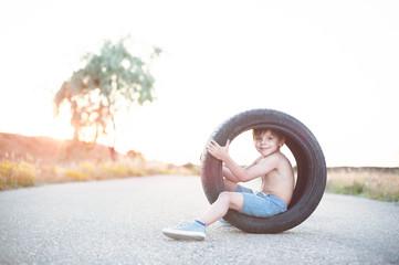 happy smiling little kid in shorts sitting inside car tire on empty asphalt road