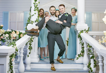 Gay wedding. One groom carrying the other down the steps of the front porch, embellished with flower garlands. Female guests clad in similar blue dresses standing behind, smiles on their faces.