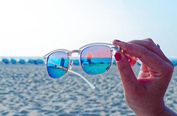 Sonnenbrille mit dem Hotel Neptun in Warnemünde im Hintergrund am Strand im Sonnenschein von einer Hand gehalten
