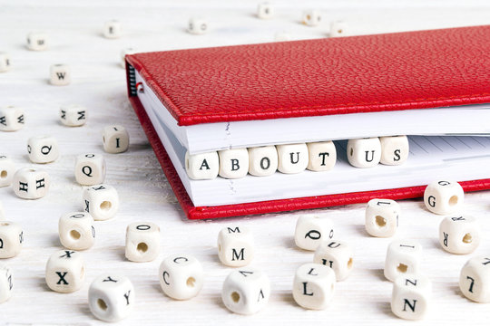 Phrase About us written in wooden blocks in red notebook on white wooden table.