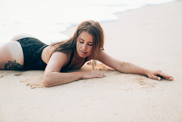 Close-up portrait of a young beautiful girl lying on the beach in a swimsuit, lips, face, hands and body in the sand. The European settles down on the tropical island