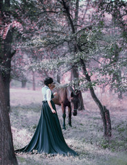 Princess in a vintage dress with a long train, walking with a horse. Photo of a brunette girl with a back without a face. The background is fantastic, a fabulous forest
