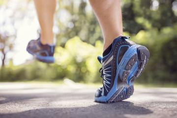 Feet of runner running or jogging on a road in summer