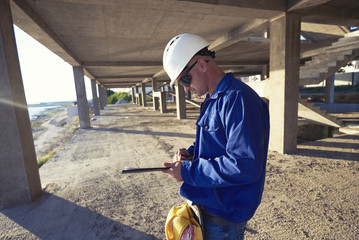Happy builder holding clipboard while working outdoors. Close up of man builder european wearing helmet glasses. Happy young worker holding a clipboard and taking some notes.