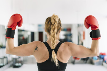 Unrecognizable woman in bowing gloves flexing arms