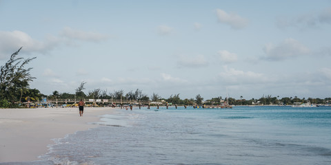 Carlisle Bay beach in Bridgetown, Barbados, unidentified man running along the water.