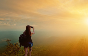 Female tourists with backpack on the mountain are taking photos.