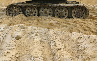 old iron caterpillar in wet sand. Rusty steel wheels and caterpillar tape of a large  bulldozer, tank, excavator, in damp sand and puddles.