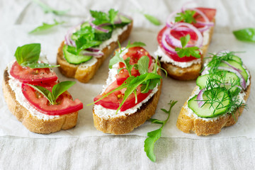 Bruschetta or sandwiches with tomatoes, cucumbers and cream cheese, decorated with greens.