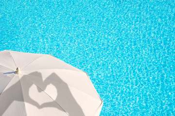 Shadows of hands forming a heart on a white parasol, blue swimming pool water background, summer concept