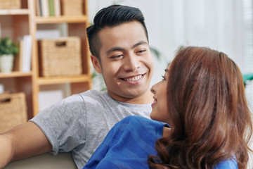 Young Asian man and woman cuddling on couch at home and looking at each other with love
