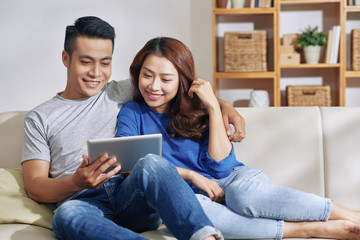 Beautiful Asian young couple embracing and chilling on couch at home while watching tablet together