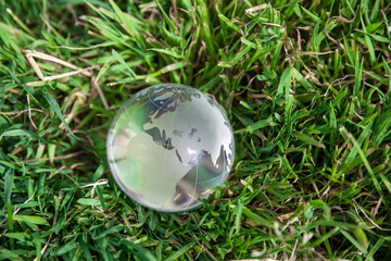glass globe on grass symbol of green & eco environment