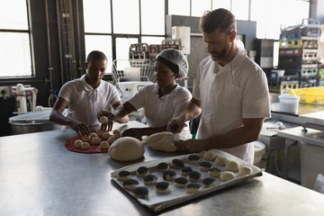 Male baker with coworkers preparing dough