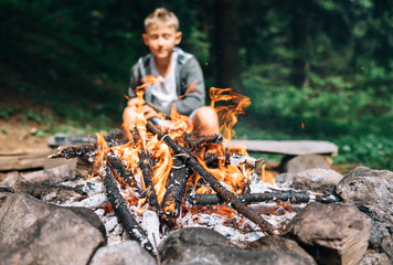 Boy sits near campfire. Summer camping time