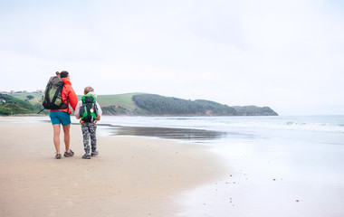 Walking travel with child. Mother and son walks together on sandy beach on the famous Camino del Norte Way, Spain
