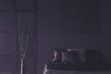 Metal dekor next to bed in dark unicolor bedroom interior with mockup of poster. Real photo