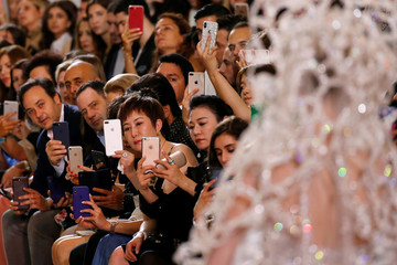Guests take pictures with their mobile phones as a model presents a creation by designer Elie Saab as part of his Haute Couture Fall/Winter 2018/2019 fashion show in Paris