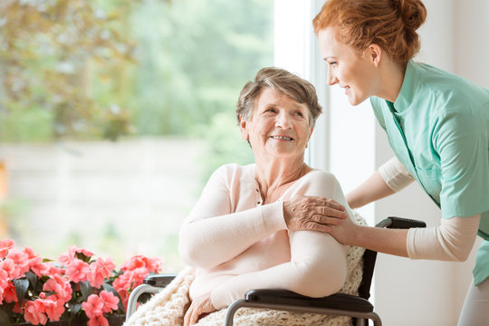 Young nurse helping an elderly woman in a wheelchair. Nursing home concept