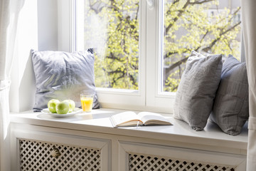 Grey cushions, book, apples and orange juice on window sill in white interior. Real photo