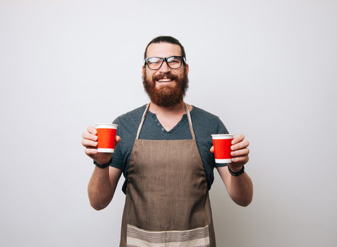 Happy bearded barista wearing apron and glasses on white background, holding two red paper cups. Hipster man smiling at the camera.