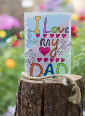 """Paper with text """"I love my DAD"""" is on a wooden log among a blossom nature."""
