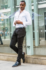Young African American Man with beard, wearing white shirt, black pants, leather shoes, holding hands in front, standing against glass wall on street in Manhattan, New York, relaxing..