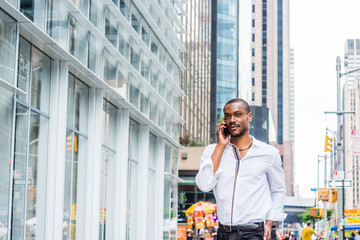 Young African American Man with beard traveling in New York, wearing white shirt, walking on street in Midtown of Manhattan, talking on cell phone. Modern high buildings, busy street on background