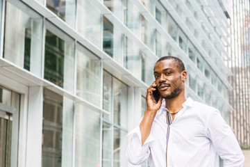 Young African American Man with beard traveling in New York, wearing white shirt, walking passing by modern office building on street in Midtown of Manhattan, talking on cell phone. .