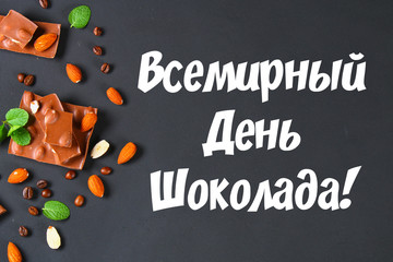 chocolate with almonds on dark grey background. Text in Russian World Chocolate Day.