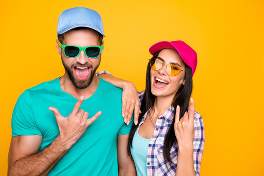 Portrait of funky crazy students in modern eyeglasses gesturing rock and roll symbols isolated on vivid yellow background. Clothes color bright creative concept