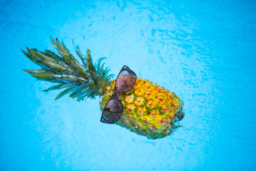 Pineapple with sunglasses in the pool, holiday feeling Wall mural