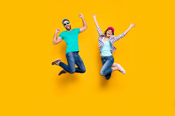 Portrait of lucky successful couple jumping with raised fists celebrating victory wearing denim outfit isolated on bright yellow background. Energy luck success concept Wall mural
