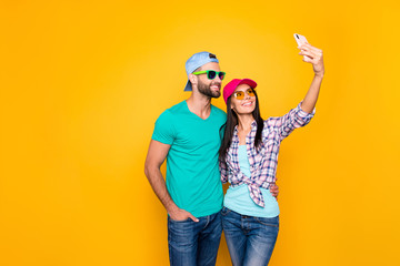 Portrait with copy space of stylish trendy couple shooting selfie on front camera of smart phone having video-call online meeting isolated on bright yellow background