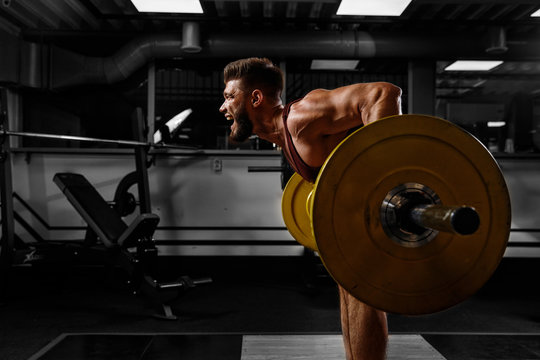 Sports background. Young athlete lifts barbell to his chest. Concept workout