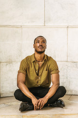 Young African American Man with beard, wearing green short sleeve shirt, black pants, leather shoes. legs crossed, sitting on marble ground by wall on campus in New York, raising head, looking up..