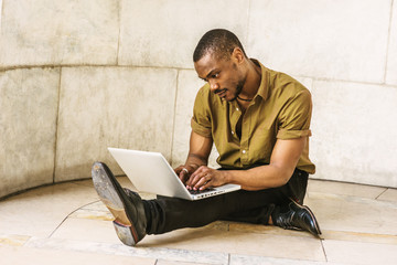 Young African American Man studying in New York, wearing green short sleeve shirt, black pants, leather shoes, sitting legs crossed on marble ground by wall on campus, working on laptop computer