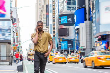 Young African American Man traveling in New York, wearing green short sleeve shirt, walking on busy street in Times Square of Manhattan, talking on cell phone. High buildings, cars on background..