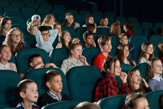 Group of stylish teenagers and children expressing facial emotions in movie theatre. Smiling spectators watching cartoon with steadfast eyes and sitting in comfortable blue chairs.