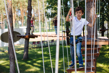 Fun pastime. Cheerful preteen boy enjoying himself at a rope park while walking down the trails