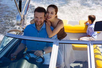 Happy vacation. Charming young woman spending a day on yacht with her husband and son while the man sailing the boat and the boy observing the views