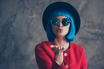 Portrait of lovely cute girl in summer glasses bright blue wig blowing air kiss with pout lips palm at camera isolated on grey background