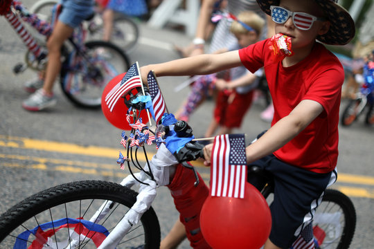 A boy rides a decorated bicycle down Main Street during the annual Fourth of July parade in Barnstable Village