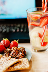 Office employee with laptop, healthy snack, water with strawberry and cucumber. Having strawberries, peanut, walnut, crispbread while working.