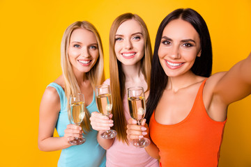 Self portrait of charming girls with beaming smiles holding glasses with alcohol beverage in hands shooting selfie on front camera having online meeting isolated on vivid yellow background