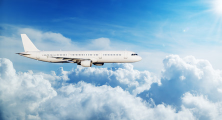 Commercial airplane jetliner flying above clouds Wall mural