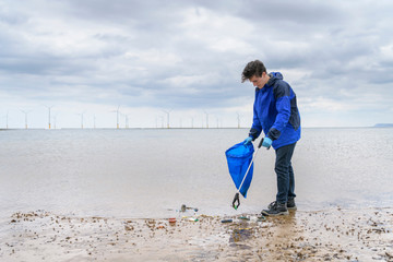 Man using litter picker to remove plastic pollution collected on beach, North East England, UK