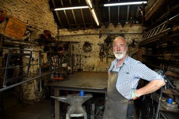 Blacksmith with hands on hips in blacksmiths shop, portrait